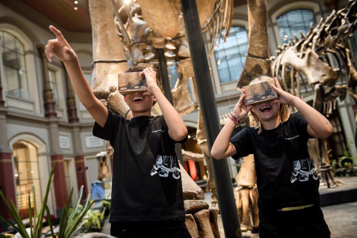 Zwei Kinder mit Google Cardboard Brillen unter dem Giraffatitan brancai