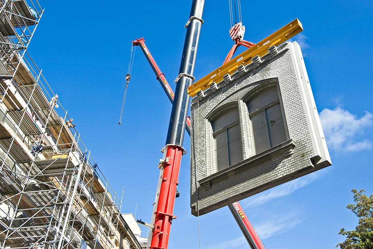 Kran hebt einen Betonblock der Ostflügelfassade des Museums