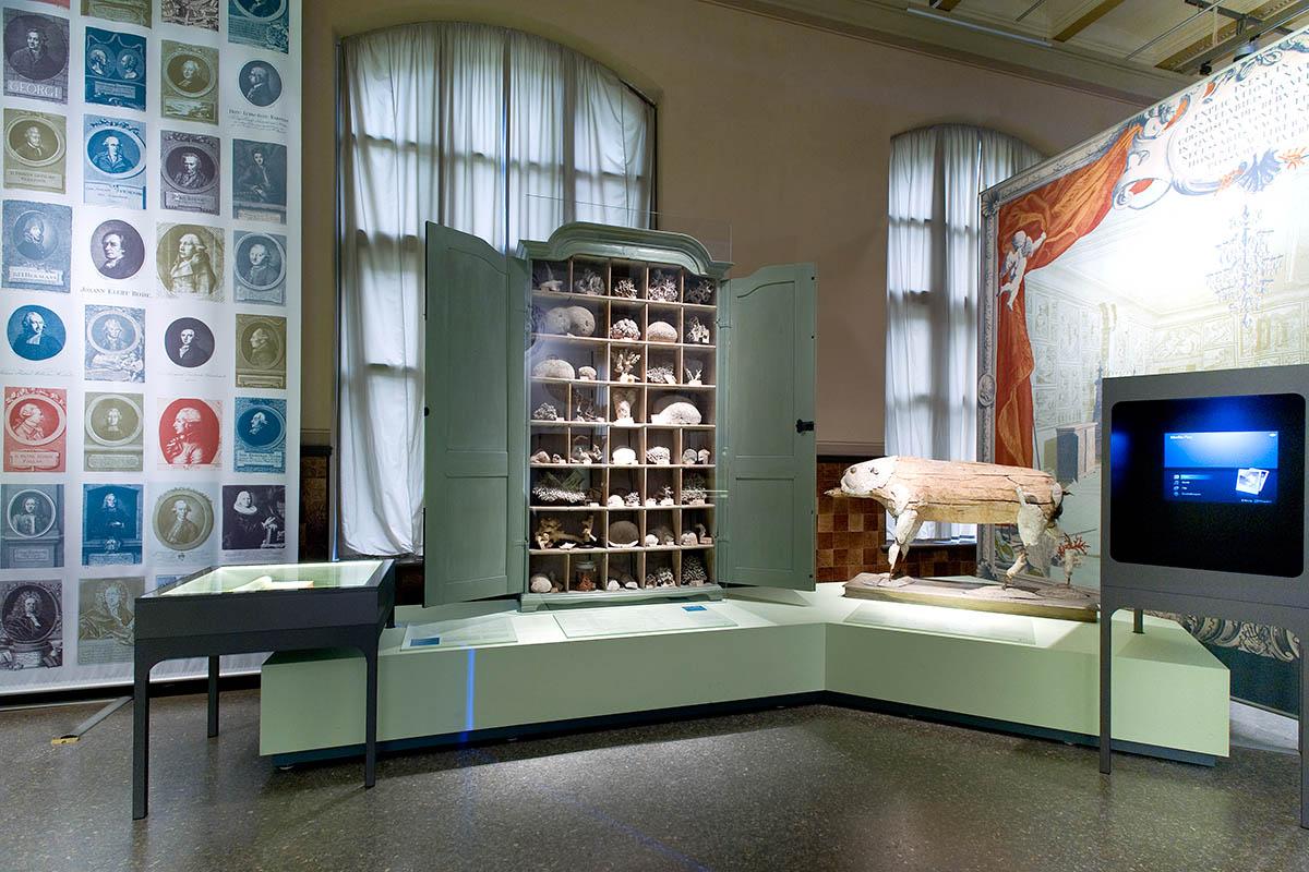 Das Foto gibt einen Einblick in die Ausstellung, im Zentrum steht ein geöffneter Kabinettschrank.