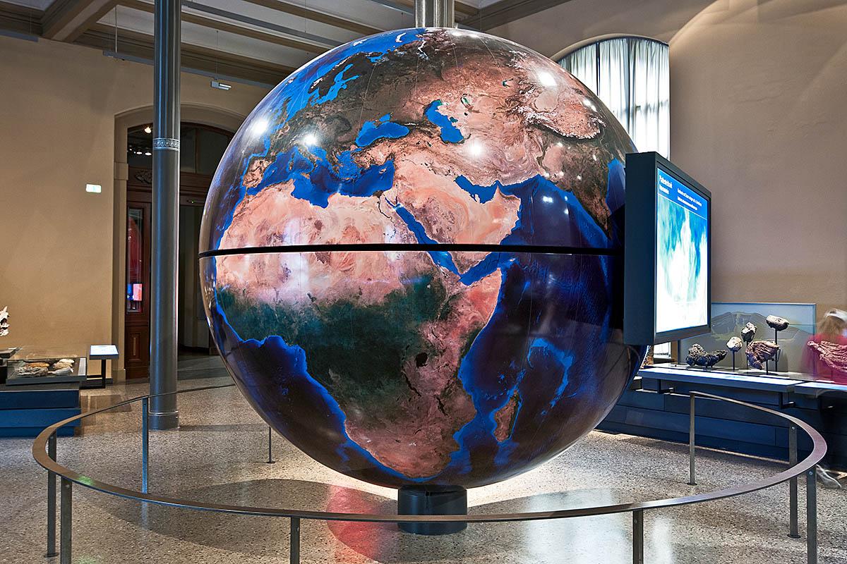 Das Foto zeigt den drei Meter hohen Globus, an welchem ein Bildschirm angebracht ist, der Animationen und Filmsequenzen zu den Themen der Ausstellung zeigt.