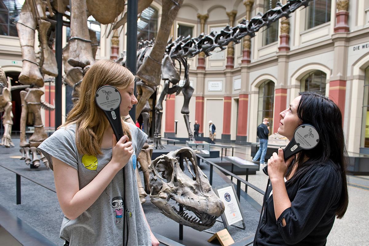 Zwei Besucherinnen mit Audioguide im Sauriersaal des Museums für Naturkunde