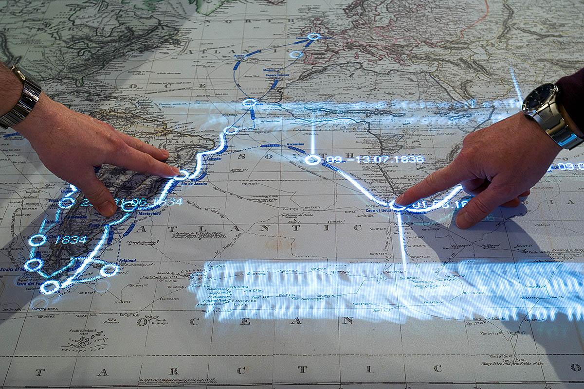 """Das Foto zeigt den interaktiven Kartentisch in der Ausstellung, welcher bei Berührung die Reiseroute Darwins auf dem Forschungsschiff """"Beagle"""" nachzeichnet."""