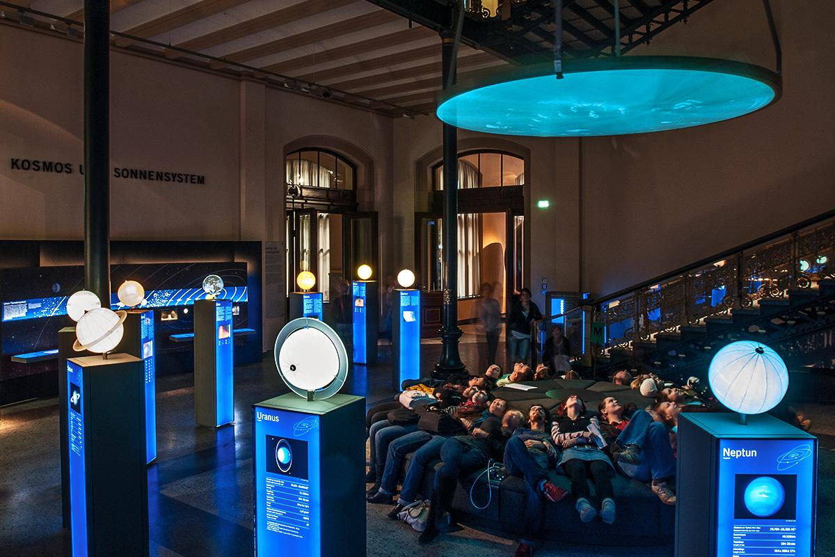 Besucher haben auf der Liege-Insel Platz genommen und betrachten die multimediale Show zur Entstehung des Universums und der Erde.