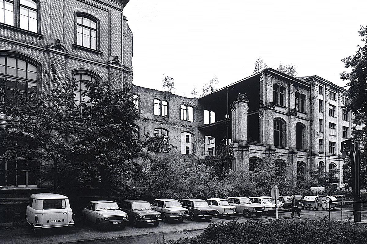 Das Foto zeigt den zerstörten Ostflügel des Gebäudes mit davor parkenden Autos.