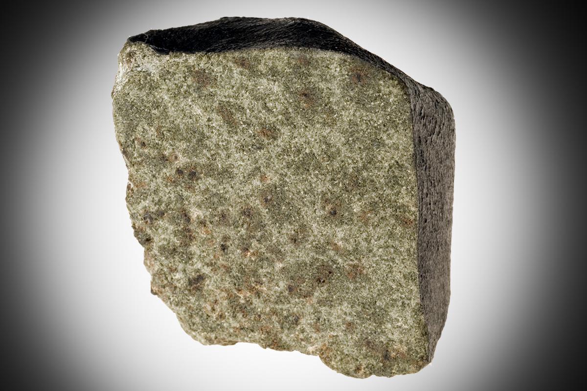 Das Foto zeigt einen Marsmeteoriten, er ist aus unterschiedlichen Mineralien zusammengesetzt und hat eine hellgrüne bis hellbraune melierte Farbigkeit.